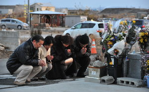Japanese praying for tsunami victims