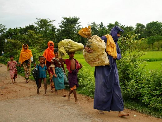Rohingyas walk along the road to reach to the refugee camp