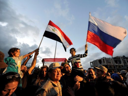 People celebrate with Russian and Syrian flags inside Waer district, after rebel fighters and their families evacuated the besieged Waer district in the central Syrian city of Homs, May 21, 2017 Reuters