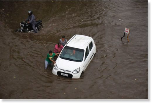 Indian men push a car through a flooded street in Ahmadabad.