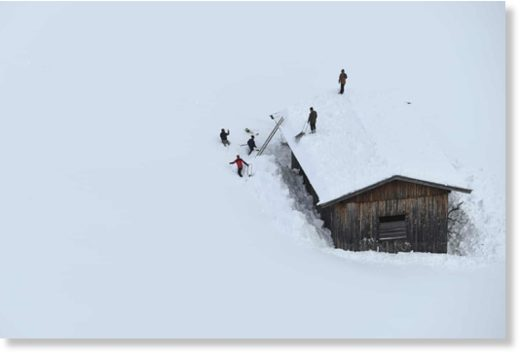 Men clean a roof from snow in Lofer, Austria