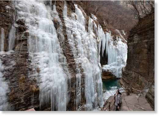 A tourist enjoying the scenery of icefall at Yuntai Mountain scenic spot in Jiaozuo, central China's Henan Province